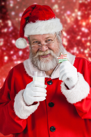 Cheerful Santa Claus holding glass of milk and star shape cookie against white snow and stars on red