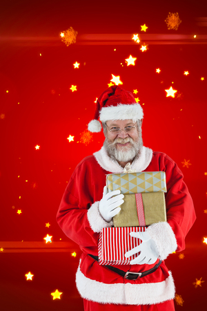 Cheerful Santa Claus holding Christmas presents against bright star pattern on red Stock Photo