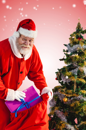 Santa Claus putting presents in bag by Christmas tree against white light dots on red