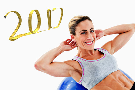 sit up: Fit woman doing sit ups on blue exercise ball smiling at camera against white background with vignette