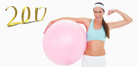 Cheerful fit woman flexing muscles with fitness ball against white background with vignette