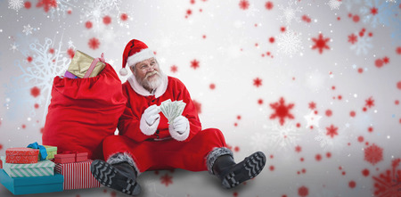 Santa Claus sitting by Christmas gifts counting bills against snowflake pattern