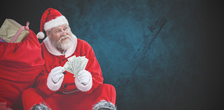 Santa Claus sitting by sack full of gifts counting currency notes against dark background