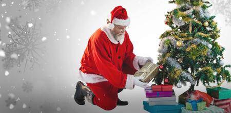 Santa Claus arranging presents near Christmas tree against snowflake pattern Stock Photo