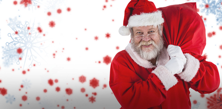 Portrait of Santa Claus holding Christmas sack against snowflake pattern Stock Photo