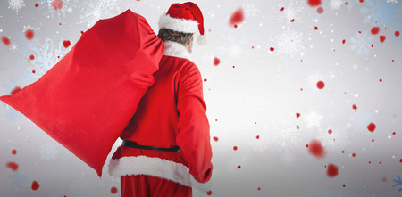 Santa Claus carrying red bag full of gifts against snowflake pattern Stock Photo