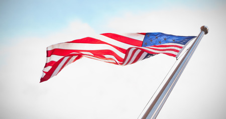 national identity: American flag against blue sky with clouds Stock Photo