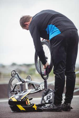 Cyclist repairing a BMX bike in skatepark