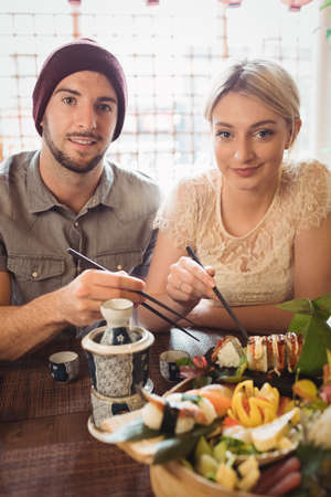 Portrait of couple having sushi in restaurant