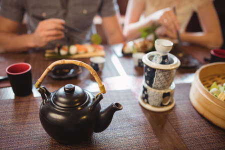 Teapot and mug on dining table in restaurant