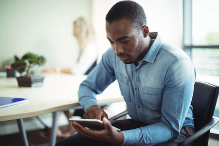technology: Business executive using digital tablet in office