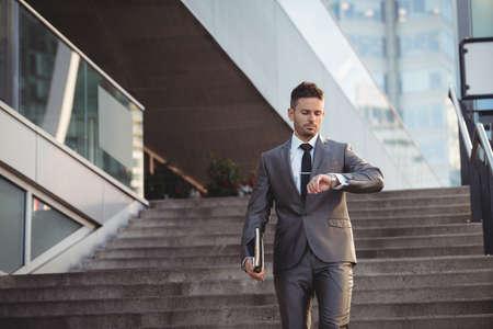 down the stairs: El hombre de negocios que controla el tiempo mientras se camina por las escaleras en la oficina