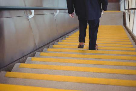 bajando escaleras: Hombre de negocios con un diario caminando por las escaleras en la oficina