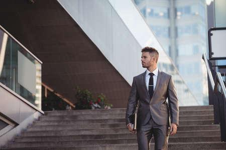 down the stairs: Hombre de negocios con un diario caminando por las escaleras en la oficina