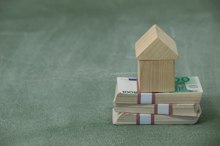 house exchange: Model house on a pile of money against green background