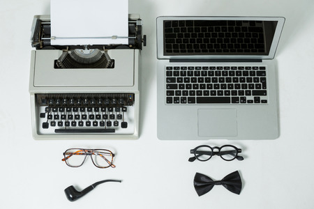 smoking pipe: Vintage typewriter and modern laptop with spectacles, smoking pipe and bow on white background Stock Photo