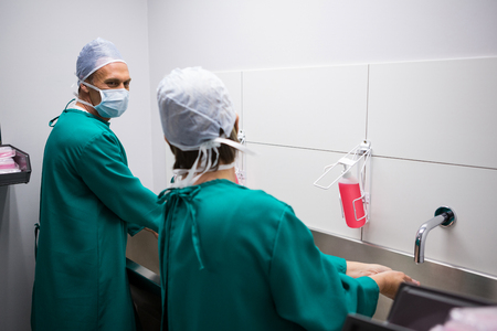 Surgeons interacting with each other while washing hands in hospital
