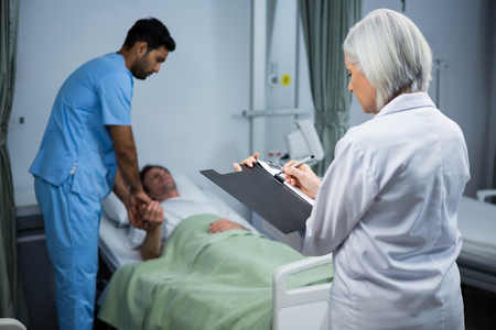 Doctor and surgeon consulting patient in ward of hospital Stock Photo