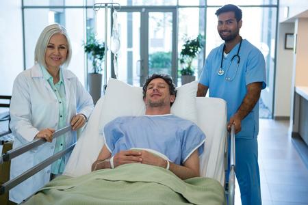 paciente en camilla: Retrato de médicos de pie mientras el paciente acostado en la camilla de emergencia en el hospital