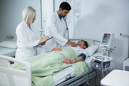 Doctor and examining a patient with stethoscope in hospital