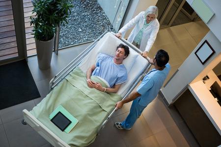 paciente en camilla: Los médicos que interactúan mientras el paciente acostado en la camilla de emergencia en el hospital