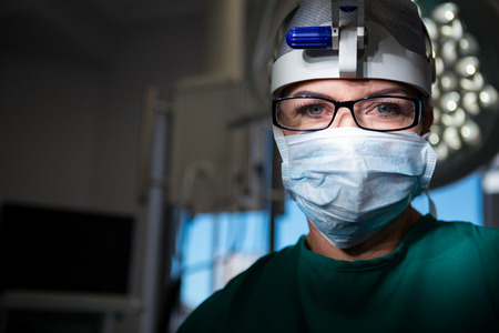 Portrait of female surgeon wearing surgical mask in operation theater Stock Photo