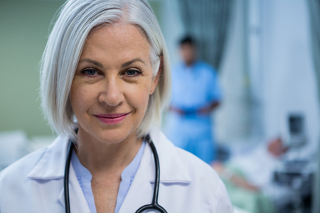 Portrait of female doctor smiling in ward of hospital Stock Photo