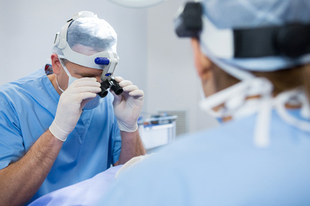 Surgeons wearing surgical loupes while operating patient in operation theater Stock Photo