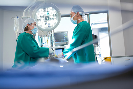 an operative: Surgeons interacting while operating patient in operation theater Stock Photo