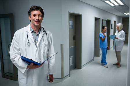 medical man: Portrait of doctor holding medical report in corridor at hospital Stock Photo