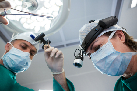 Surgeons holding surgical tool while operating in operation theater Stock Photo