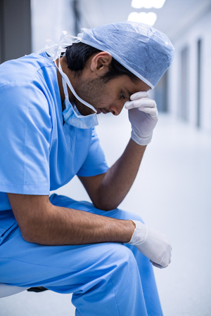 Sad surgeon sitting on a chair in hospital corridor Stock Photo