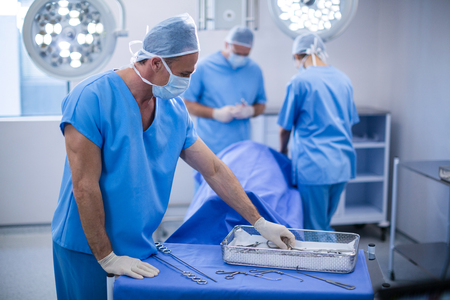 surgical tray: Surgeon removing surgical tools from tray in operation room at the hospital Stock Photo