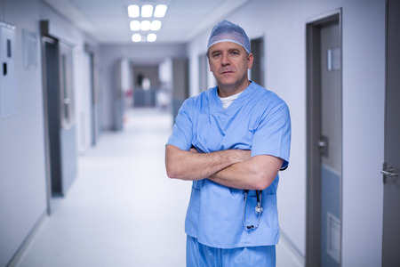 Portrait of surgeon standing with arms crossed in hospital corridor