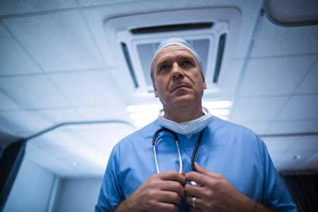 surgical cap: Surgeon holding stethoscope at hospital Stock Photo