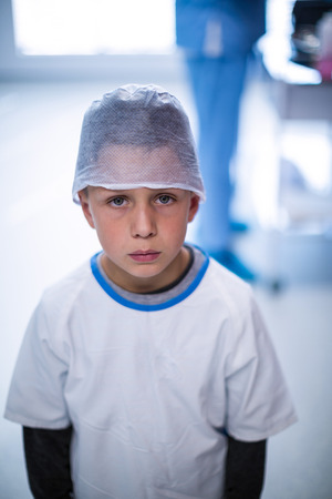 surgical cap: Portrait of upset boy in surgical cap at hospital Stock Photo
