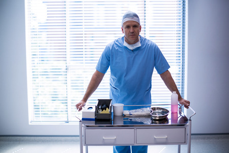 hospital trolley: Portrait of male surgeon holding trolley at hospital Stock Photo
