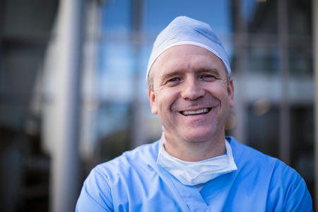surgical cap: Portrait of male surgeon smiling at camera in hospital corridor