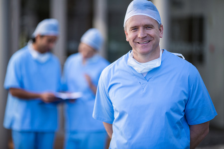 Portrait of male surgeon smiling at camera in hospital corridor
