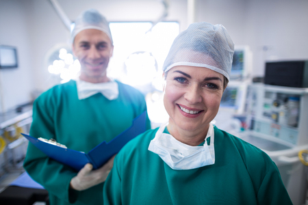 Portrait of smiling surgeons in operation room at hospital Stock Photo