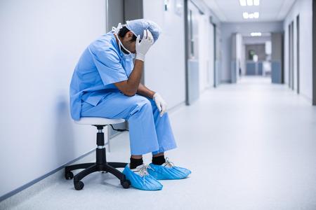 Sad surgeon sitting on a chair in hospital corridor Stockfoto