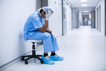 Sad surgeon sitting on a chair in hospital corridor Reklamní fotografie