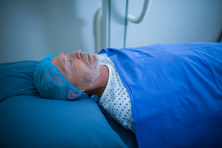 surgical cap: Patient relaxing on bed in x-ray room at hospital Stock Photo
