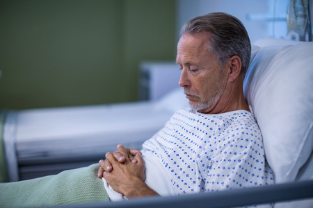hospital patient: Sick patient sitting on bed at hospital