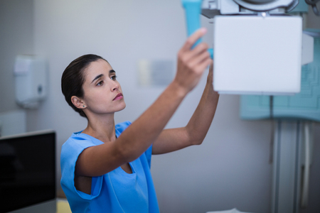Nurse adjusting x-ray machine at the hospital