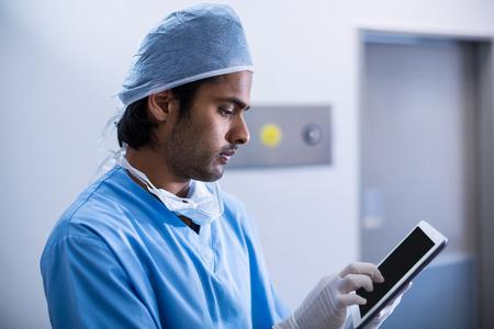 Chirurgien en utilisant tablette numérique dans la salle d'opération à l'hôpital
