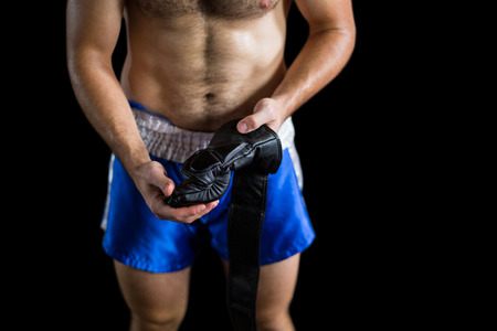 grappling: Mid section of boxer wearing grappling gloves against black background