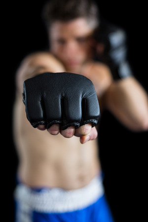 Boxer performing boxing stance against black background Stock Photo