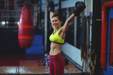 female boxer: Portrait of excited female boxer posing after victory in fitness