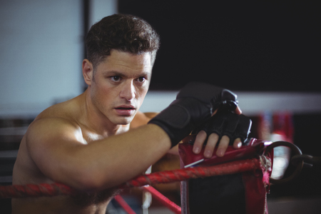 grappling: Tired boxer leaning on boxing ring